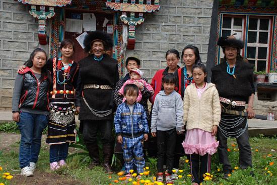 图为 娅米一家的幸福照(左起为:娅米小妹米玛卓玛、娅米、外公达果、外婆娅加和小侄儿达嘎、大嫂扎西、大妹娅英、大哥达玛;前排为娅米的两个侄女和大侄儿)。记者 麦正伟 摄
